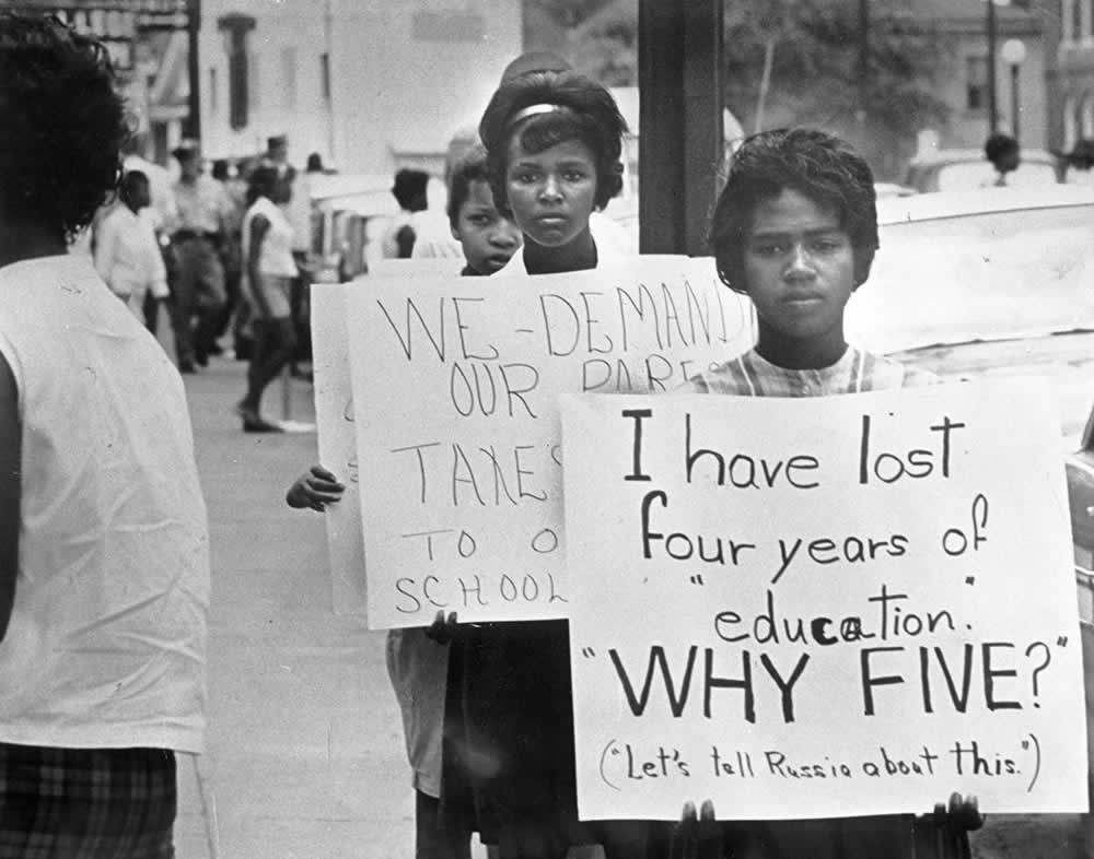 "Students protesting in Farmville, Prince Edward County, Virginia, about 1963. Note the last sentence at the end of the sign held up in front: (""Let's tell Russia about this.')."