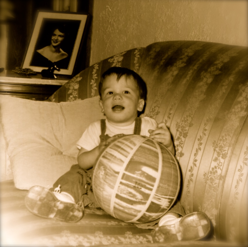 "William Bass, ""Little Dudley,"" just over a year old, at his grandparents' home in Blacksburg, VA. Behind him is a frame foto of his mother, Dorothy Ussery Bass. June 1960."