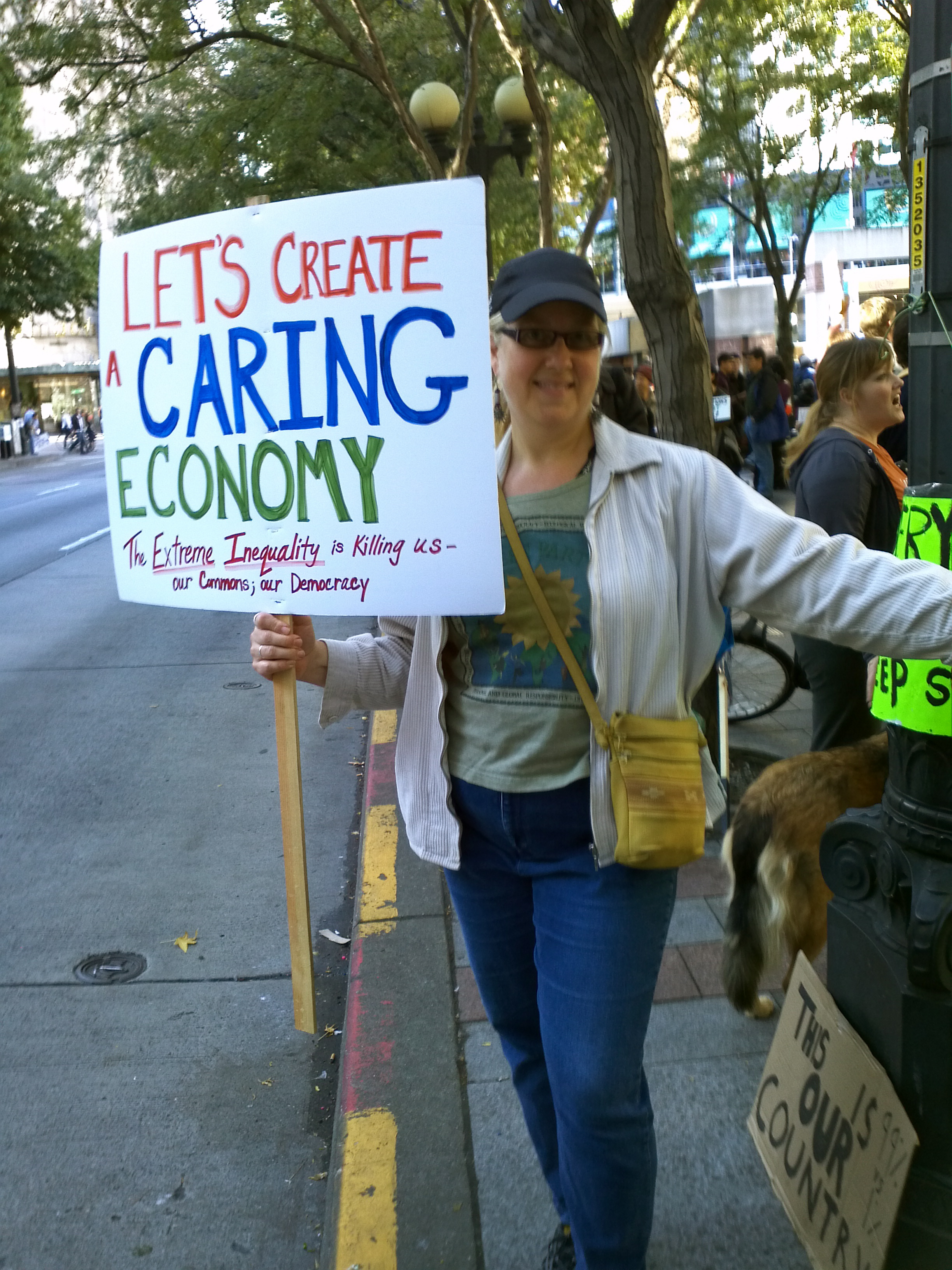 """William's friend, activist Syd Fredrickson demonstrating for """"a Caring Economy"""" during the Occupy Seattle! Rally & March on Saturday 8 October 2011. Foto by William Bass."""