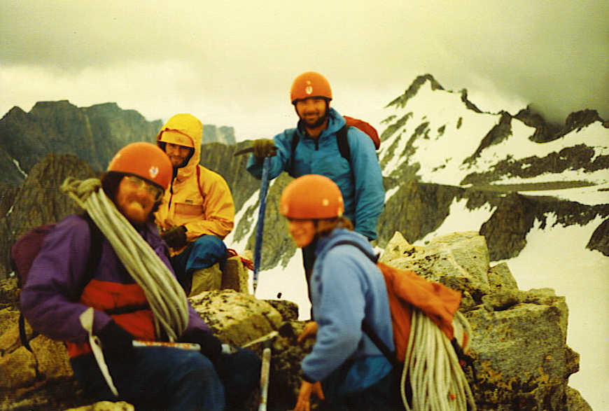Atop the summit of Iowa Peak, Wind River Mountains, in a break in the storm. Left to right (clockwise): The Author, John Toll (in yellow), Ray H. (standing), Laura B. Group Self-Portrait by William Bass.