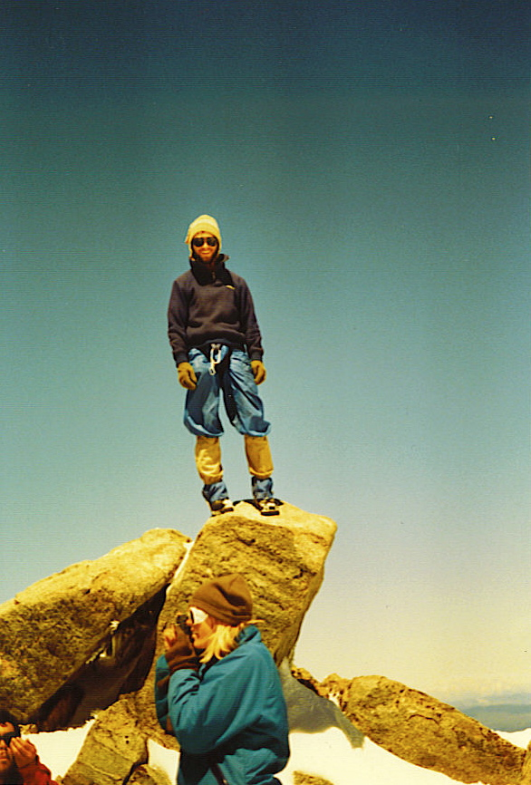 John Toll of Iowa, Assistant NOLS Instructor, atop Gannet Peak, WY, 13,804 ft., July 12, 1986. He named & led our Iowa Peak climb 4 days later. Jenn H. is in front. Photo by William Bass.