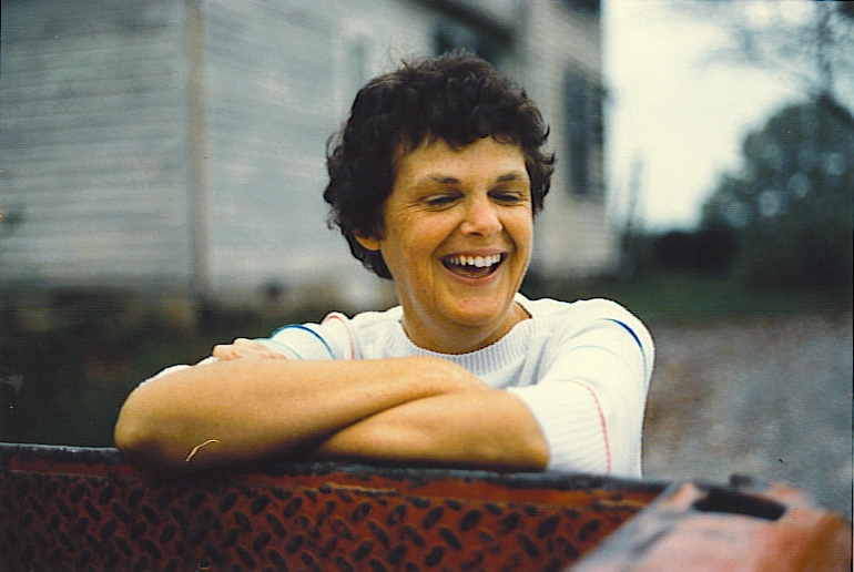 Mom at 53 in Happier Days, Riverview Farm, Rice, VA. She's leaning over the bed of our old red Ford pickup truck with the unoccupied original Bass Family Farmhouse still standing behind her. October 1984. Foto by William D. Bass.