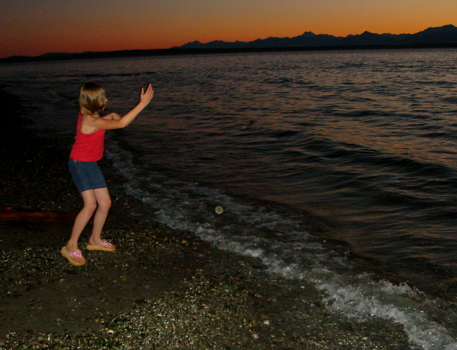 Morgan turns loose a skipping stone into Puget Sound. Across the water sit the Olympics. Carkeek Park, 16 June 2004.