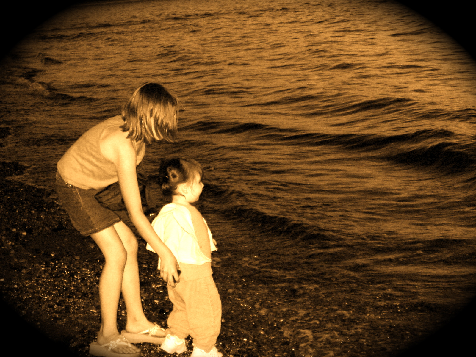 Morgan showing Talia how to skip rocks into the Sound, Carkeek Park, Seattle, June 2004.
