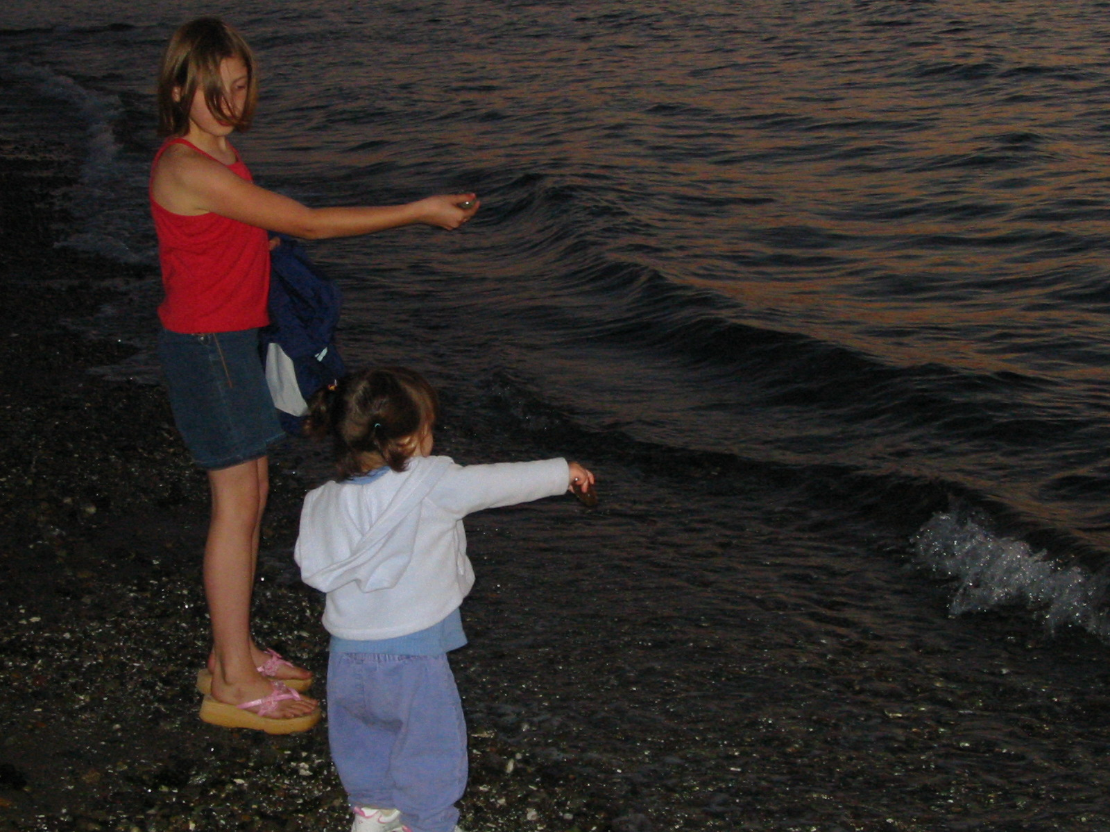 """""""There you go!"""" Morgan & Talia skipping stones at Carkeek. Wednesday 16 June 2004."""
