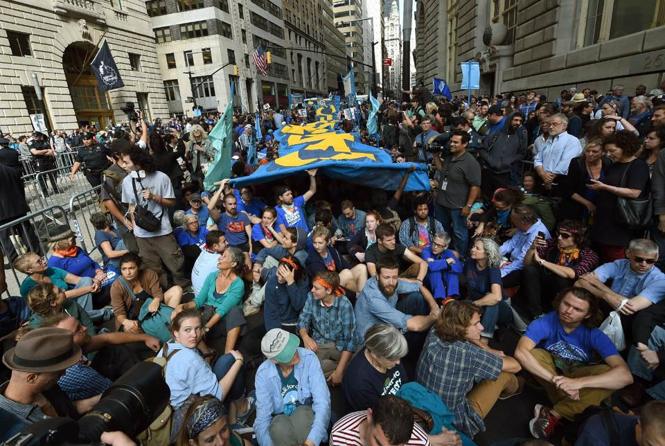 Flood Wall Street! Protestors swarm into New York City to shut down Wall Street on Monday, 22 September 2014, the day after 400-500,000 people engaged in the People's Climate March. AFP Photo/Timothy A. Clary.